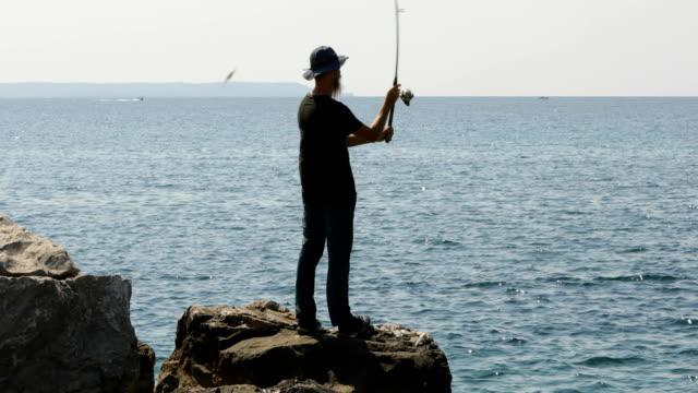 mid adult man fishing at aegean sea in greece - żabnicokształtne filmów i materiałów b-roll