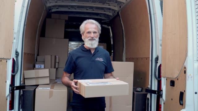 持有送貨包裹的中年男子 - postal worker 個影片檔及 b 捲影像