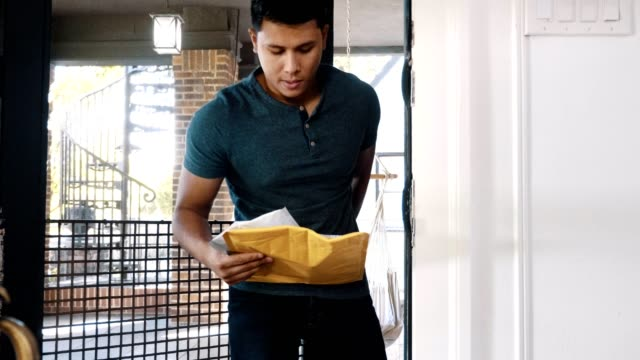 Mid adult man retrieves a package from his front porch video