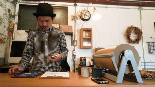Hombre adulto medio trabajando en una pequeña tienda general - vídeo