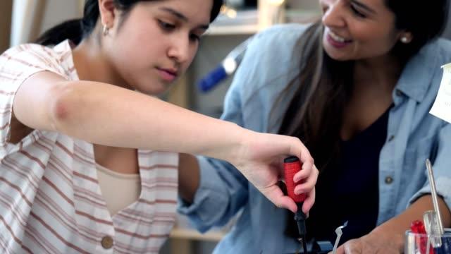 Mid adult mom helps daughter repair laptop