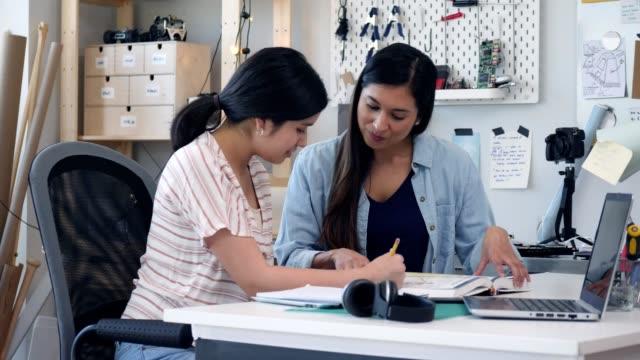 mid erwachsene mama hilft teenager-tochter bei hausaufgaben - highschool lehrer stock-videos und b-roll-filmmaterial