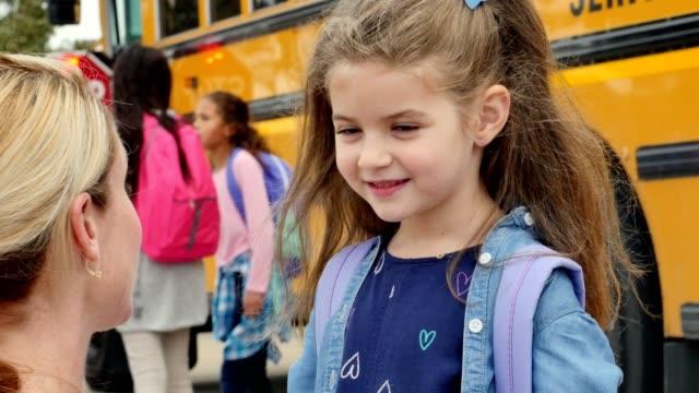 Meados adulto mãe fala com a filha de idade elementar antes a garota embarca um ônibus escolar - vídeo