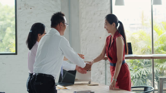 Mid Adult Taiwanese Woman Bowing and Shaking Hands After After Job Interview