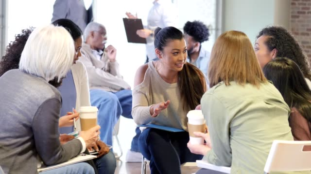 Mid adult therapist facilitates support group Confident mid adult Asian female therapist counsels a group of women during a support group meeting. She gestures as she encourages the group of women. organized group stock videos & royalty-free footage
