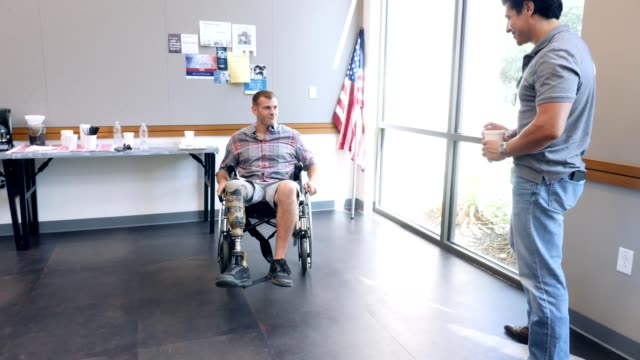 Mid adult veteran in wheelchair shows stunts to friend Confident mid adult military veteran in wheelchair spins around, performing a stunt for his friend. The men are waiting for support group meeting to begin. artificial limb stock videos & royalty-free footage