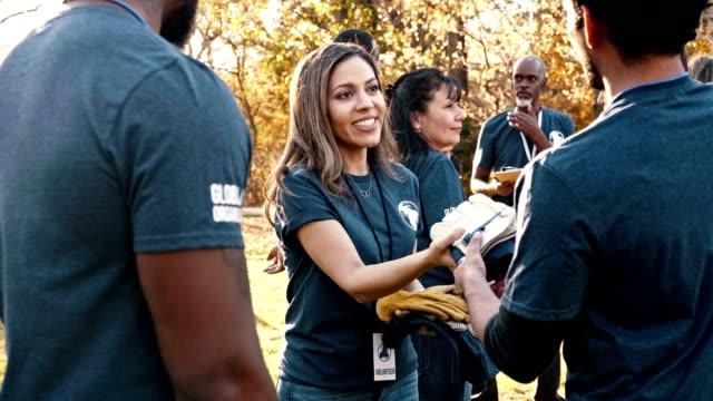 Mid adult volunteer coordinator hands supplies to volunteers during cleanup event
