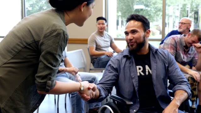 Mid adult wheelchair-bound veteran attends meeting for veterans Confident mid adult wheel-chair bound male veteran shakes hands in greeting with a female counselor while attending a group therapy session with fellow veterans. veteran stock videos & royalty-free footage