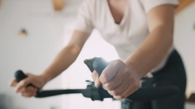 vídeos de stock e filmes b-roll de slo mo mid adult woman being exhausted after cycling on the exercise bike - treino em casa