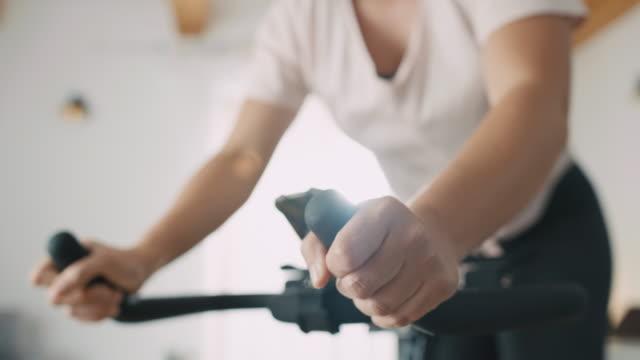 slo mo mid vuxen kvinna är utmattad efter cykling på motionscykeln - hemmaträning bildbanksvideor och videomaterial från bakom kulisserna