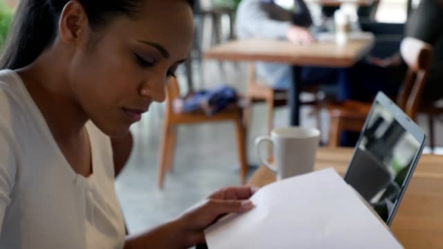 Mid adult woman complete application form in coffee shop Mid adult mixed race woman signs an application form or other document while sitting in a coffee shop. Camera moves from her signing the document up to her face. form filling stock videos & royalty-free footage