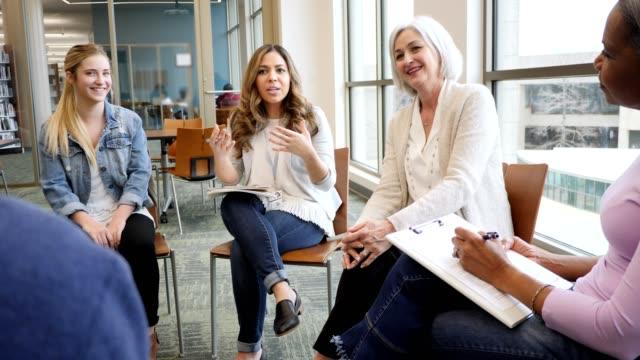 la donna adulta media discute qualcosa durante la riunione del gruppo di supporto - fragilità video stock e b–roll
