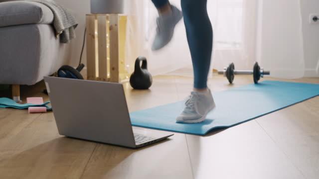 slo mo mid vuxen kvinna gör en online övningar hemma - hemmaträning bildbanksvideor och videomaterial från bakom kulisserna