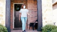 istock Mid adult woman leaves home wearing protective face mask 1251964523