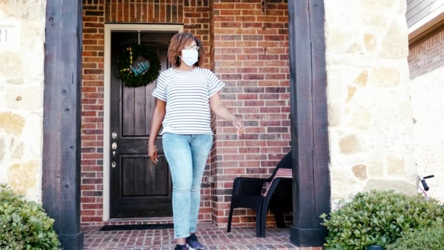 Mid adult woman leaves home wearing protective face mask