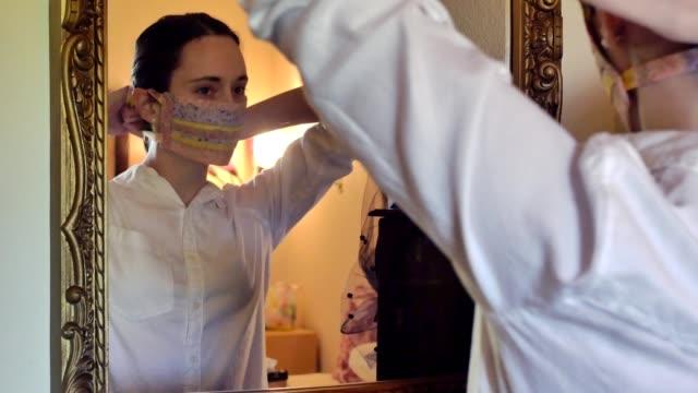 stockvideo's en b-roll-footage met een medio volwassen vrouw zet op een beschermend masker tijdens covid-19 pandemie - mirror mask