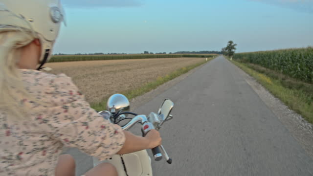 SLO MO Mid adult woman riding a scooter on country road at dusk