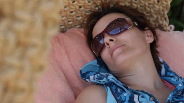 Mid adult woman sleeping in hammock in summertime video