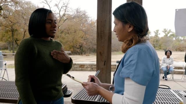 ücretsiz açık klinikte hemşire ile orta yetişkin kadın görüşmeleri - tıbbi klinik stok videoları ve detay görüntü çekimi