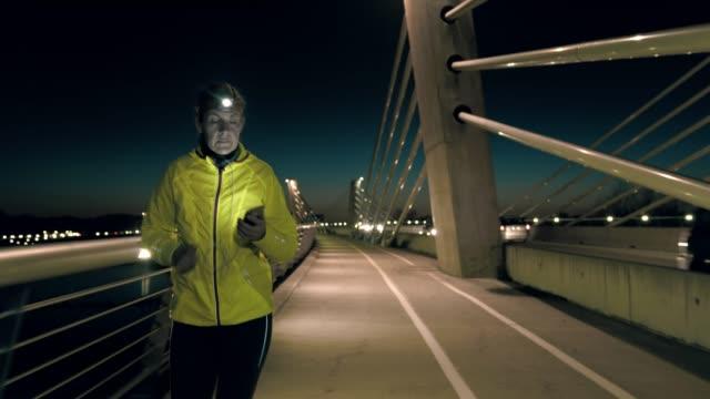 slo mo mitte erwachsene frau mit einem smartphone beim joggen über die brücke - einzelne frau über 30 stock-videos und b-roll-filmmaterial