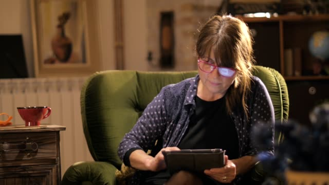 Mid age woman working online with tablet computer