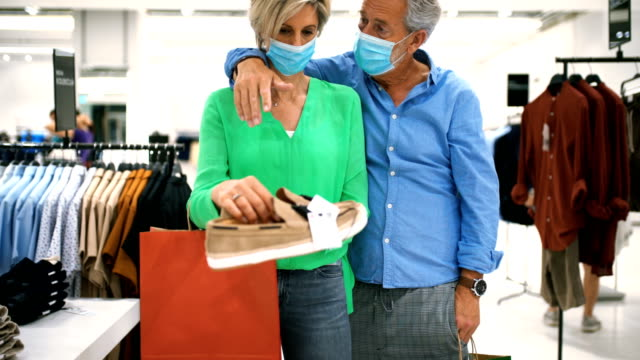 Mid aged couple in a shopping mall during coronavirus.