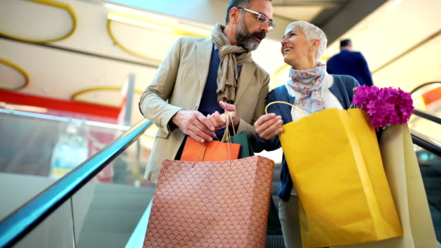 mid aged couple in a shopping mall. - borsa della spesa video stock e b–roll