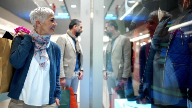 mid aged couple in a shopping mall. - krótkie włosy filmów i materiałów b-roll