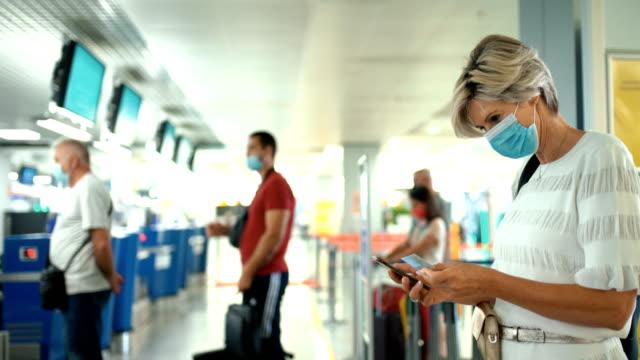 medelålders kvinna på en flygplats under coronaviruspandemi. - flygplats bildbanksvideor och videomaterial från bakom kulisserna
