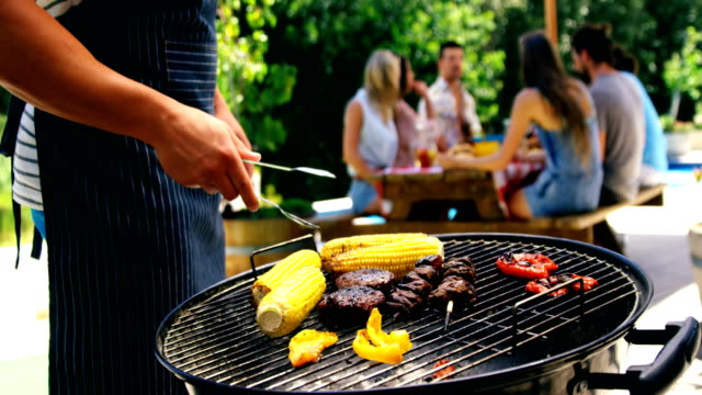mid section of man grilling corn, meat and vegetable on barbecue - grilling stock videos & royalty-free footage