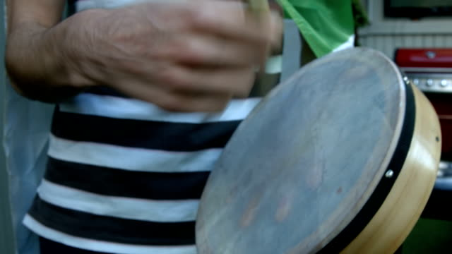 Mid section of man playing bodhran video