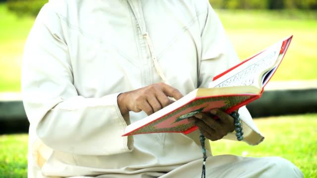 stockvideo's en b-roll-footage met mid sectie van islamitische grootvader quran in openbaar park te lezen in de ochtend - koran