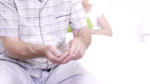 中央セクションの老人男性の錠剤を呑む - 耐久力点の映像素材/bロール