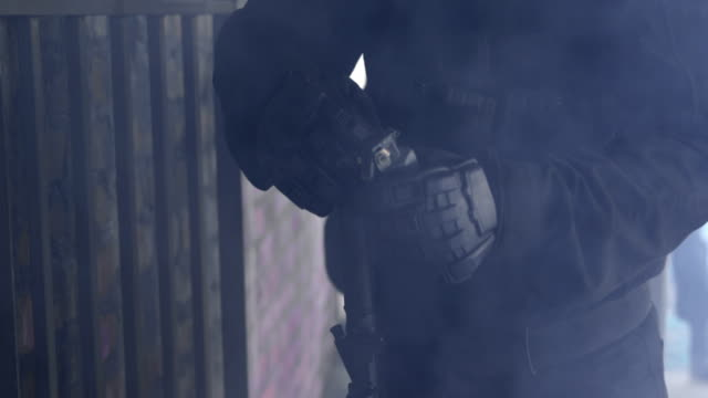 Mid section of soldier throwing smoke grenades in building during military exercise 4k video