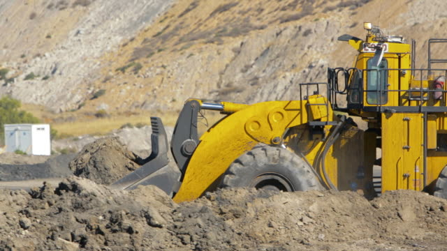 Mid Shot Bulldozer bucket dumping dirt at a coal mine A front-end loader pushes mounds of dirt at a coal mine. Mid Shot. construction equipment stock videos & royalty-free footage