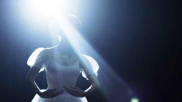 mitten av skott av en vacker ung ballerina dansa graciöst i rampljuset, mörker runt henne. hon är klädd i vit tutu klänning som gnistrar i ljuset. i slow motion. - piruett bildbanksvideor och videomaterial från bakom kulisserna