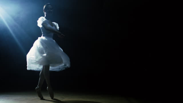 Mid Shot of a Beautiful Young Ballerina Dancing Gracefully in the Spotlight, Darkness Around Her. She's Wearing White Tutu Dress that Sparkles in the Light. In Slow Motion. video