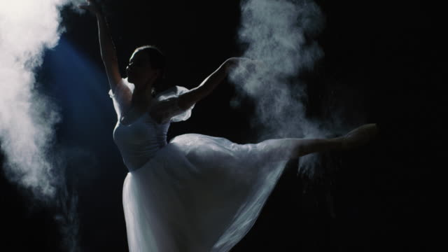Mid Shot of a Beautiful Young Ballerina Spinning Gracefully in the Spotlight. She Throws Dust Particles in the Air They Shine in the Darkness Around Her. She's Wearing White Tutu Dress that Sparkles in the Light. In Slow Motion. video