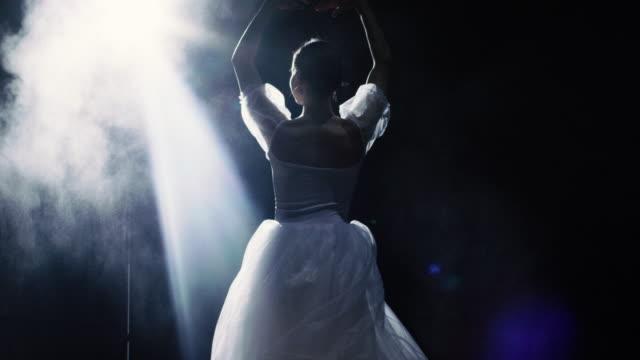 mid shot av en vacker ung ballerina spinning graciöst i rampljuset. pulver och rök lysa i mörkret runt henne. hon är klädd i vit tutu klänning som gnistrar i ljuset. i slow motion. - piruett bildbanksvideor och videomaterial från bakom kulisserna