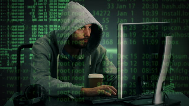 Tiro de meados de um Hacker usando capuz, sentado em seu computador Desktop. Efeitos especiais de códigos são mostrados na tela. - vídeo