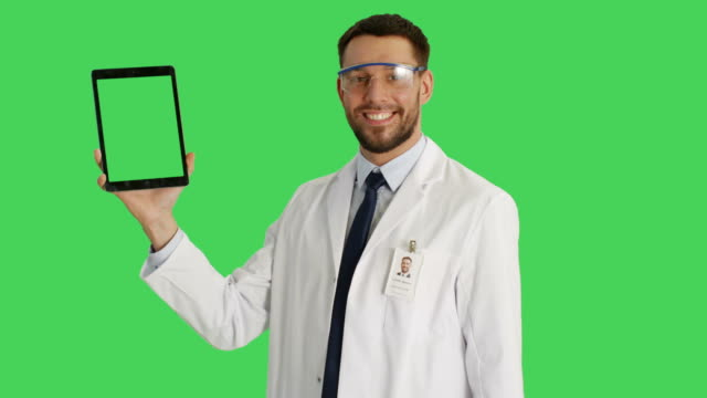 Mid Shot of a Handsome Scientist Wearing Protective Glasses Holding Tablet Computer with One Hand and Making Swiping Touching Gestures with Another. Tablet and Background are Green Screen. video