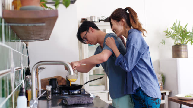 Mid shot of a young couple cooking scrambled eggs together for breakfast