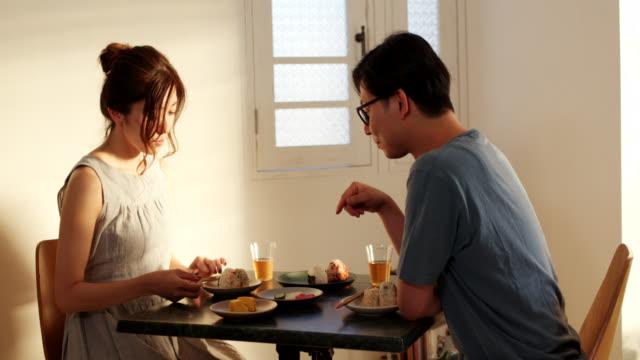 vídeos y material grabado en eventos de stock de tiro medio de una pareja joven comiendo bolas de arroz japonesas juntas en casa - casados