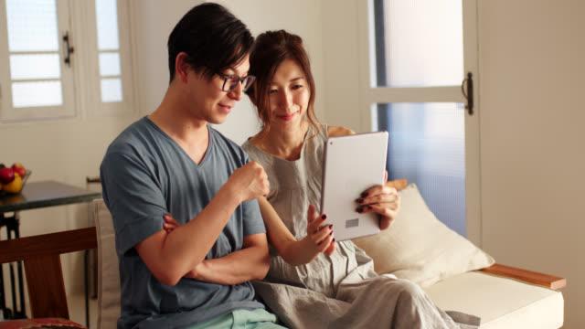 vídeos y material grabado en eventos de stock de el tiro medio de una joven pareja mirando una tableta digital en la sala de estar - casados
