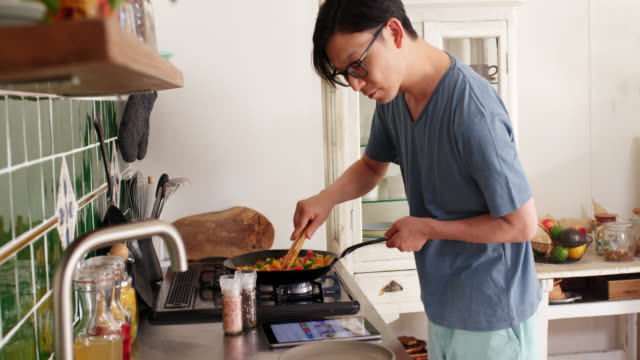 Mid shot of a young man checking a digital tablet and cooking dinner at home