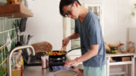 istock Mid shot of a young man checking a digital tablet and cooking dinner at home 1152255590
