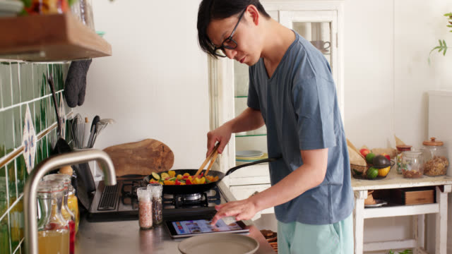 Mid shot of a young man checking a digital tablet and cooking dinner at home Mid shot of a young man checking a digital tablet and cooking dinner at home. Shot in 4K. Tokyo, Japan stir fried stock videos & royalty-free footage