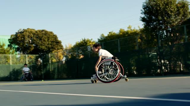 ダブルスをプレーするアダプティブテニス選手のslo moミッドショット - disabilitycollection点の映像素材/bロール