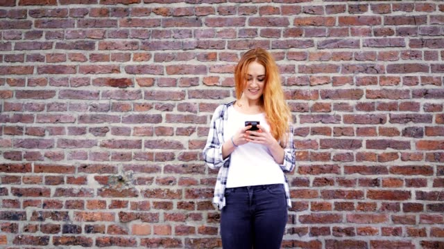 Mid shot of smiling young woman using smartphone and leaning against wall