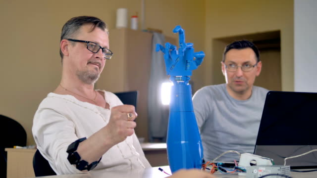 vídeos y material grabado en eventos de stock de tiro medio de los dos hombres prueba mano robótica biónica. - copiar